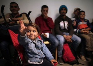 A young girl reacts moments after refugees from Syria and Irak arrived at a refugee centre in Champagne-sur-Seine, near Paris, France, September 9, 2015. France is ready to take in 24,000 refugees as part of European Union plans to welcome more than 100,000 in the next two years, the French President said on Monday, dismissing opinion polls showing public opposition to the move. REUTERS/Christian HartmannATTENTION EDITORS : FRENCH LAW REQUIRES THAT THE FACES OF MINORS ARE MASKED IN PUBLICATIONS - RTS9AZ